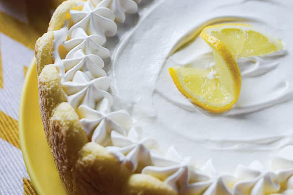 A whole cake on a yellow plate with a slice of lemon on top.