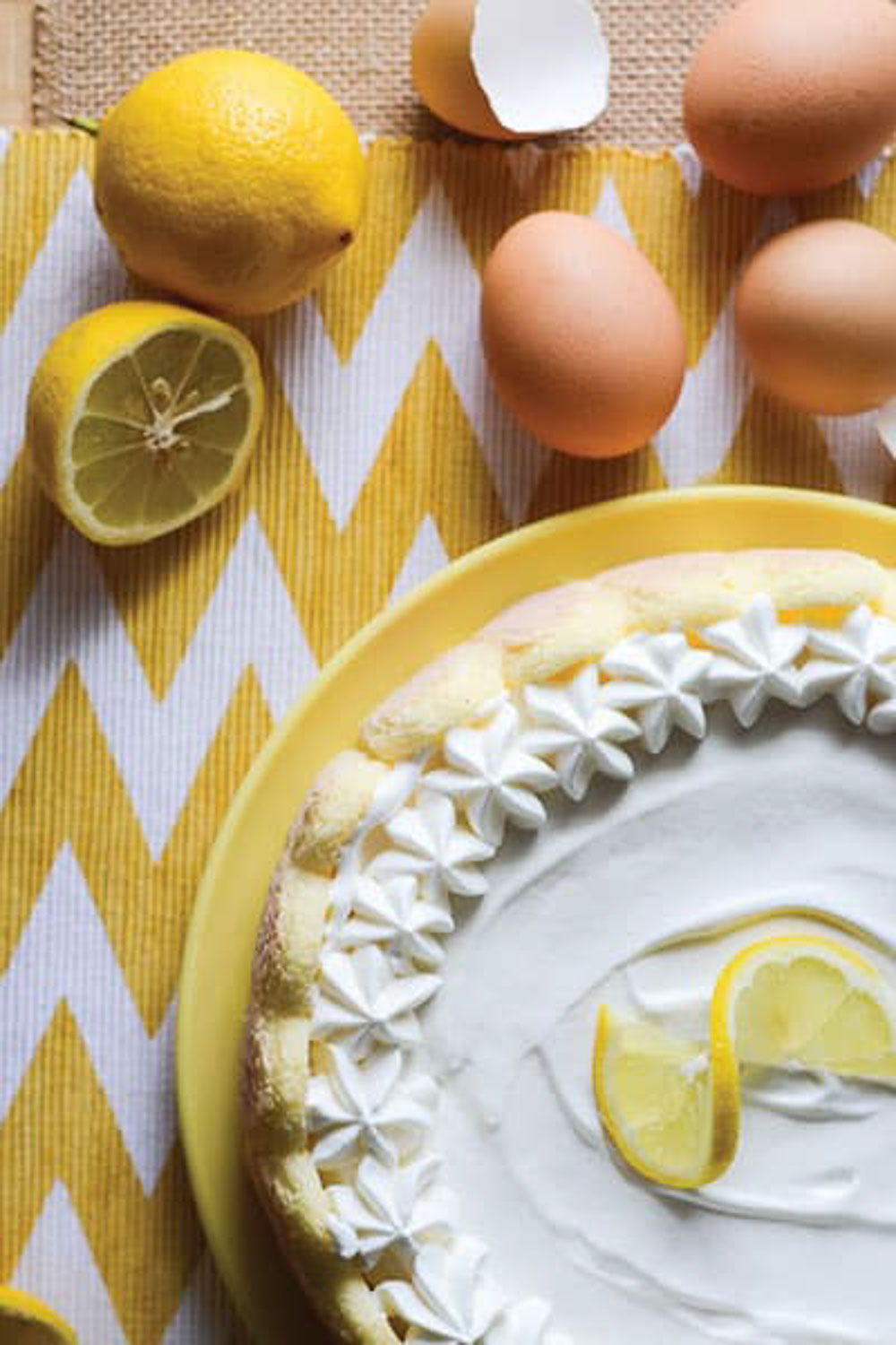 A whole  cake on a yellow plate with a slice of lemon on top with whole eggs and cut lemons on a yellow and white chevron towel.