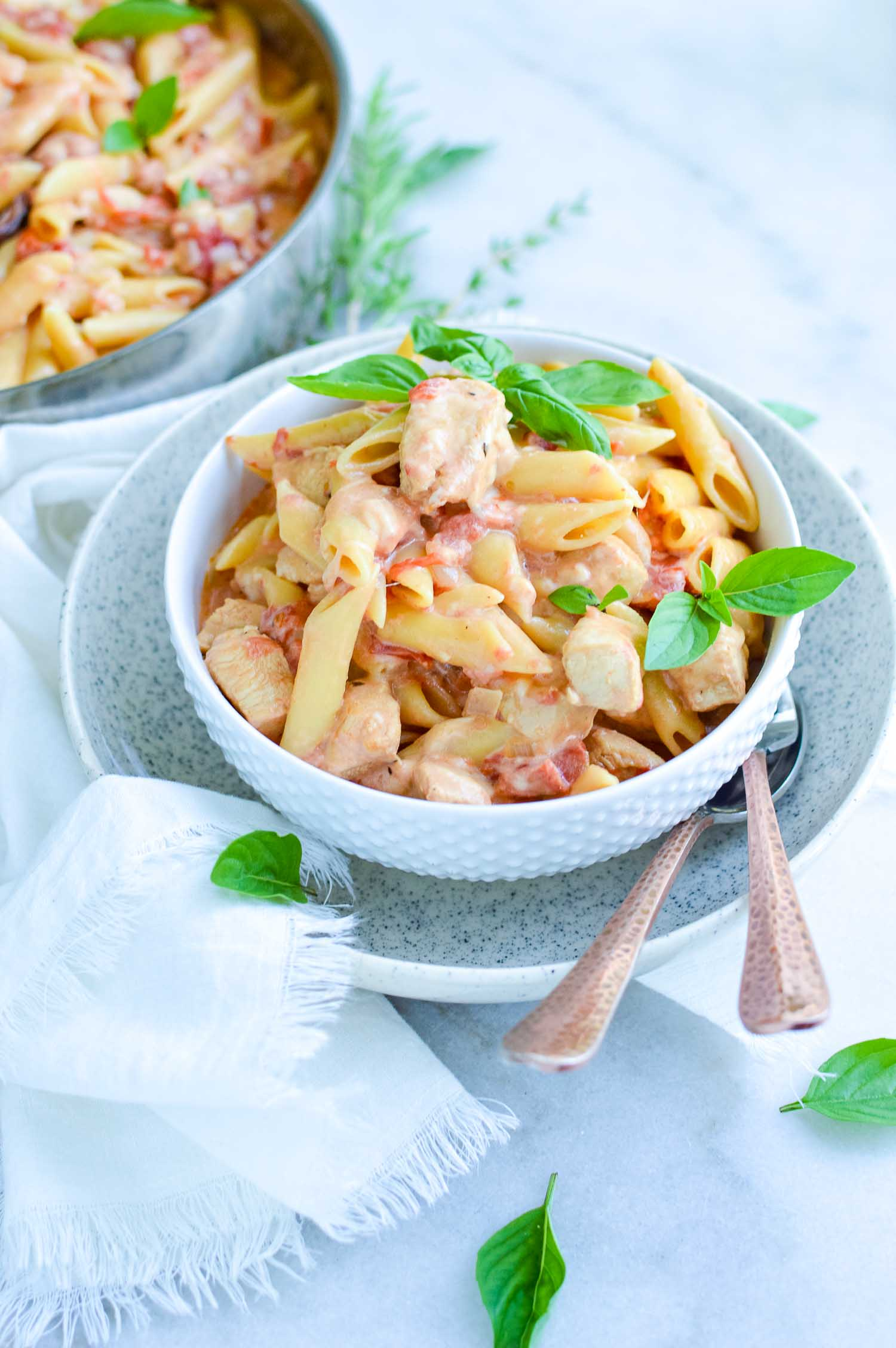 A white bowl inside a speckled bowl full of garlic chicken pasta with a silver fork in it and a spoon on the side of it with a silver pan full of extra pasta.