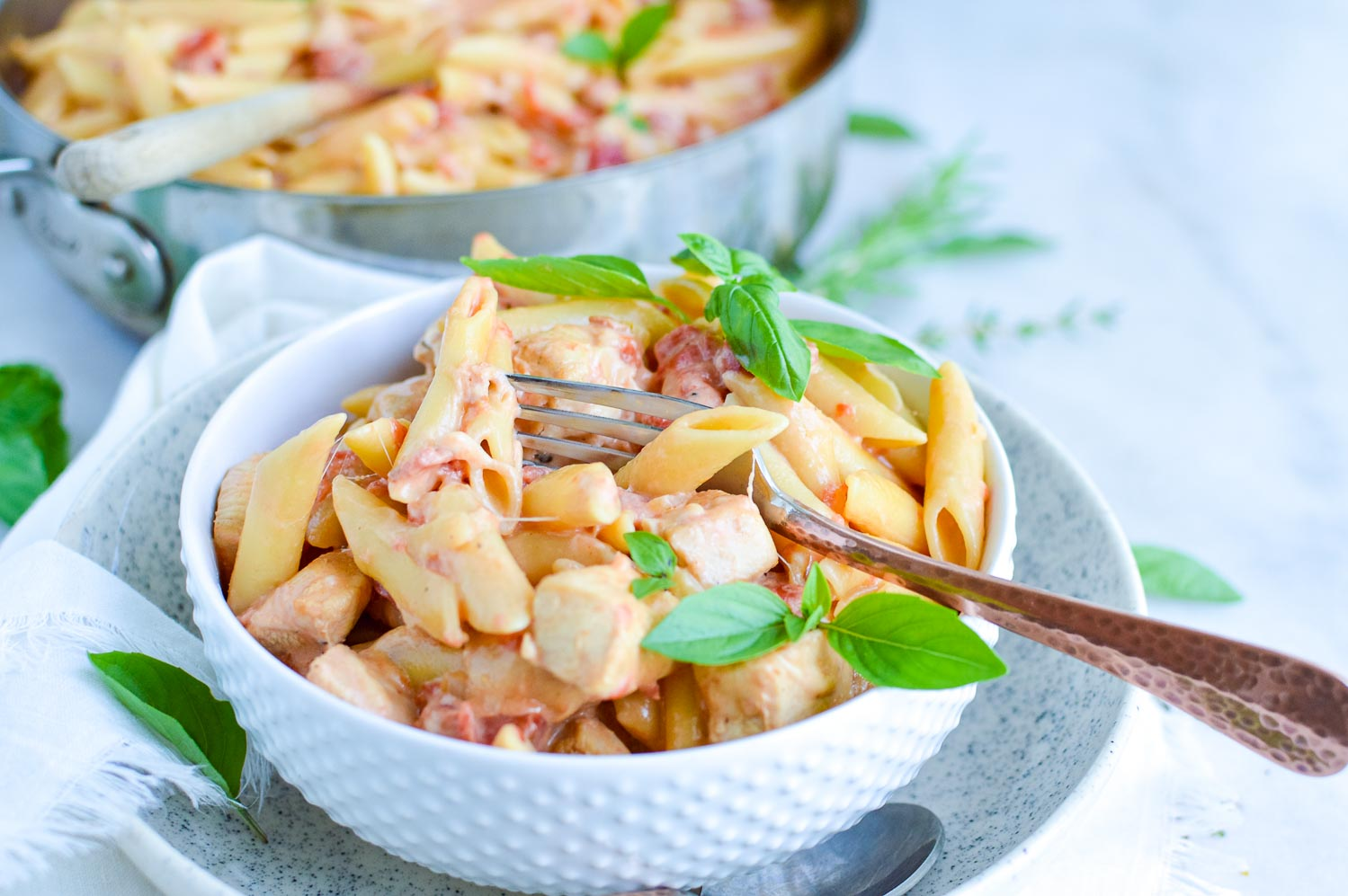 A white bowl inside a speckled bowl full of garlic chicken pasta with a silver fork in it with fresh basil around and a silver pan behind it full of pasta.