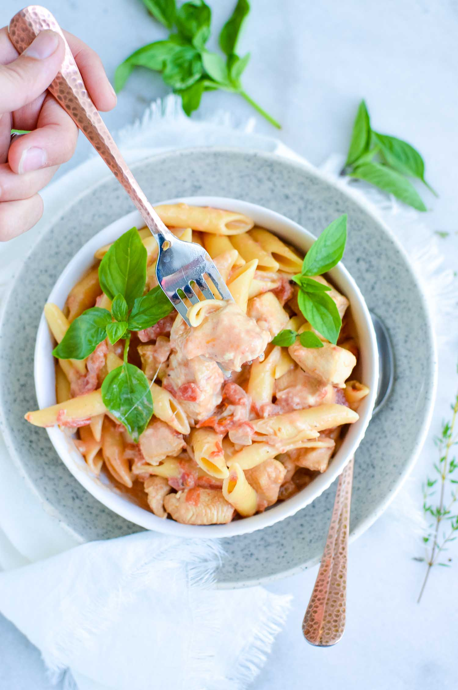 A white bowl inside a speckled bowl full of pasta, cheese, tomatoes and spices with a silver fork in it spearing chicken and a spoon on the side of it with fresh basil around the bowls.