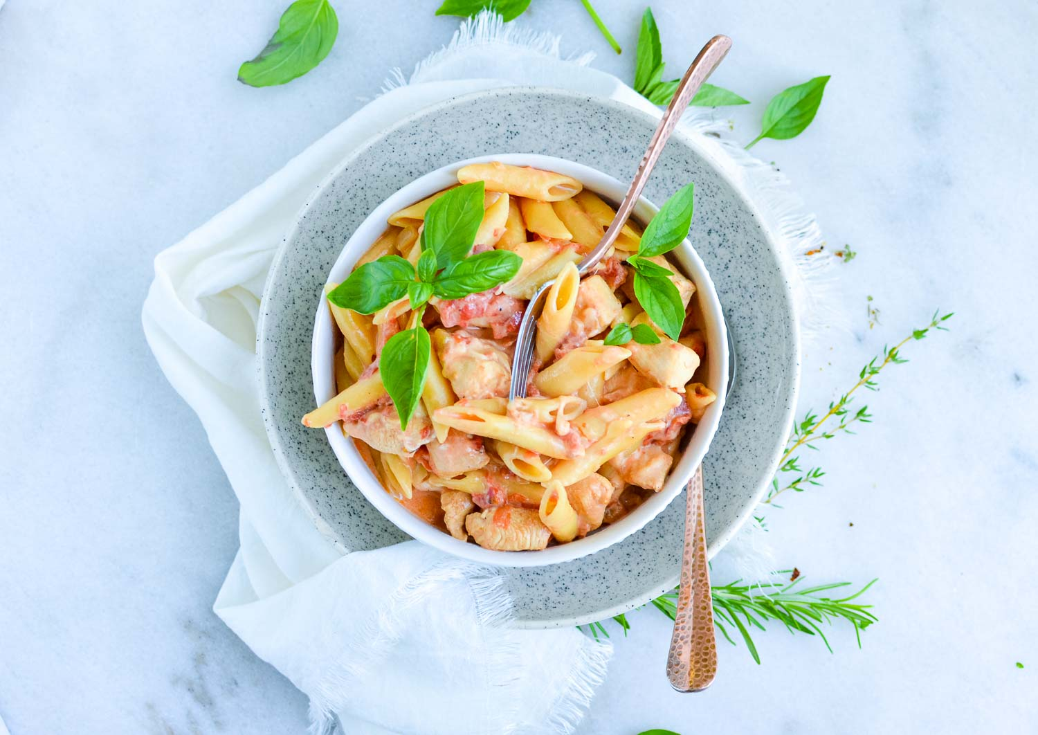 A white bowl inside a speckled bowl full of pasta, cheese, tomatoes and spices with a silver fork in it and a spoon on the side of it with fresh herbs and a white towel around it.