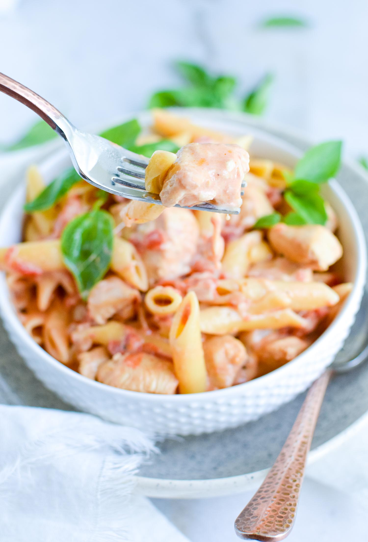 A white bowl inside a speckled bowl full of pasta, cheese, tomatoes and spices with a silver fork lifted up with a piece of chicken on it.