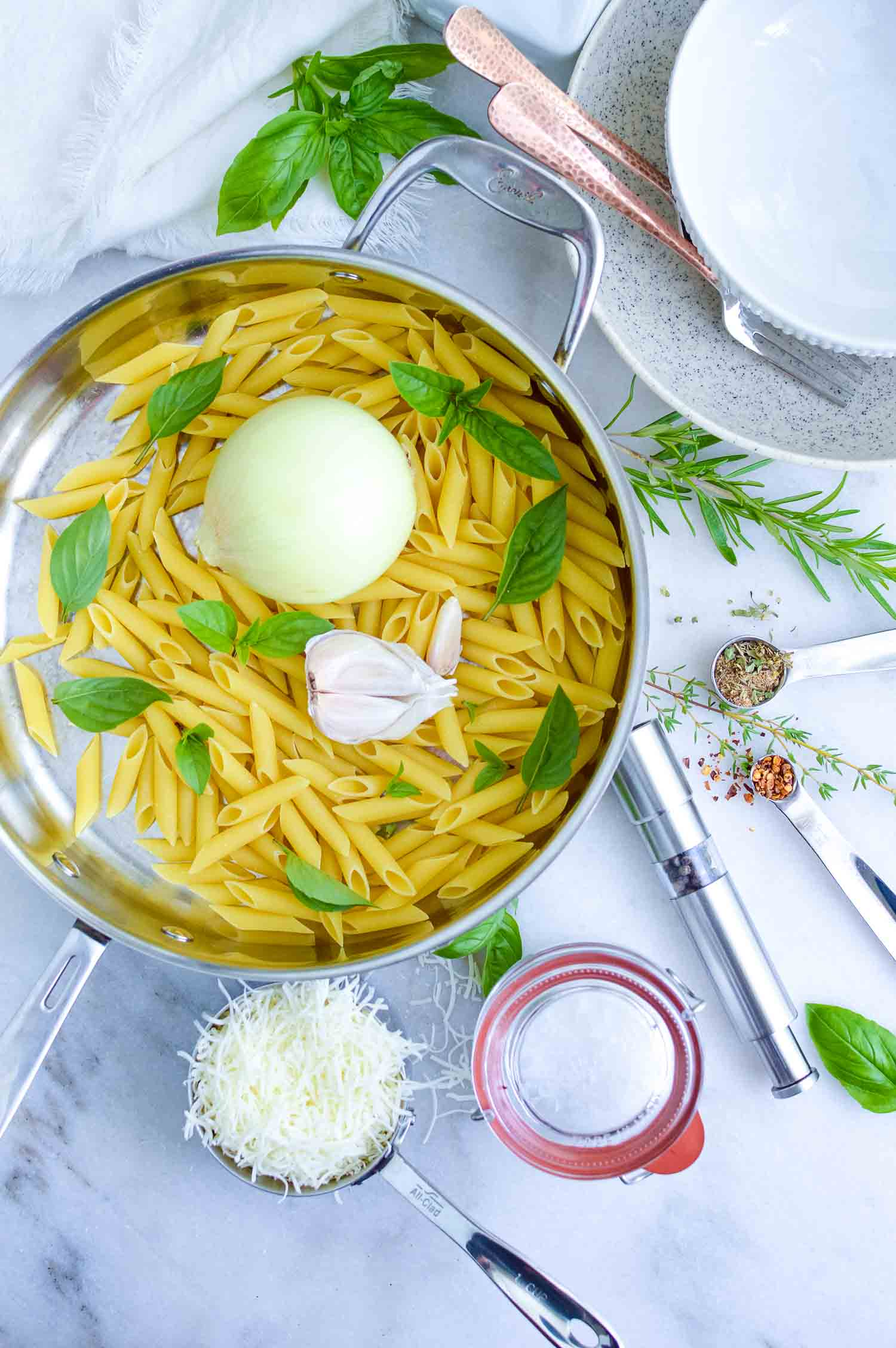 A silver pan with uncooked pasta, basil, onion, garlic in it with spices, cheese and water in containers around it.