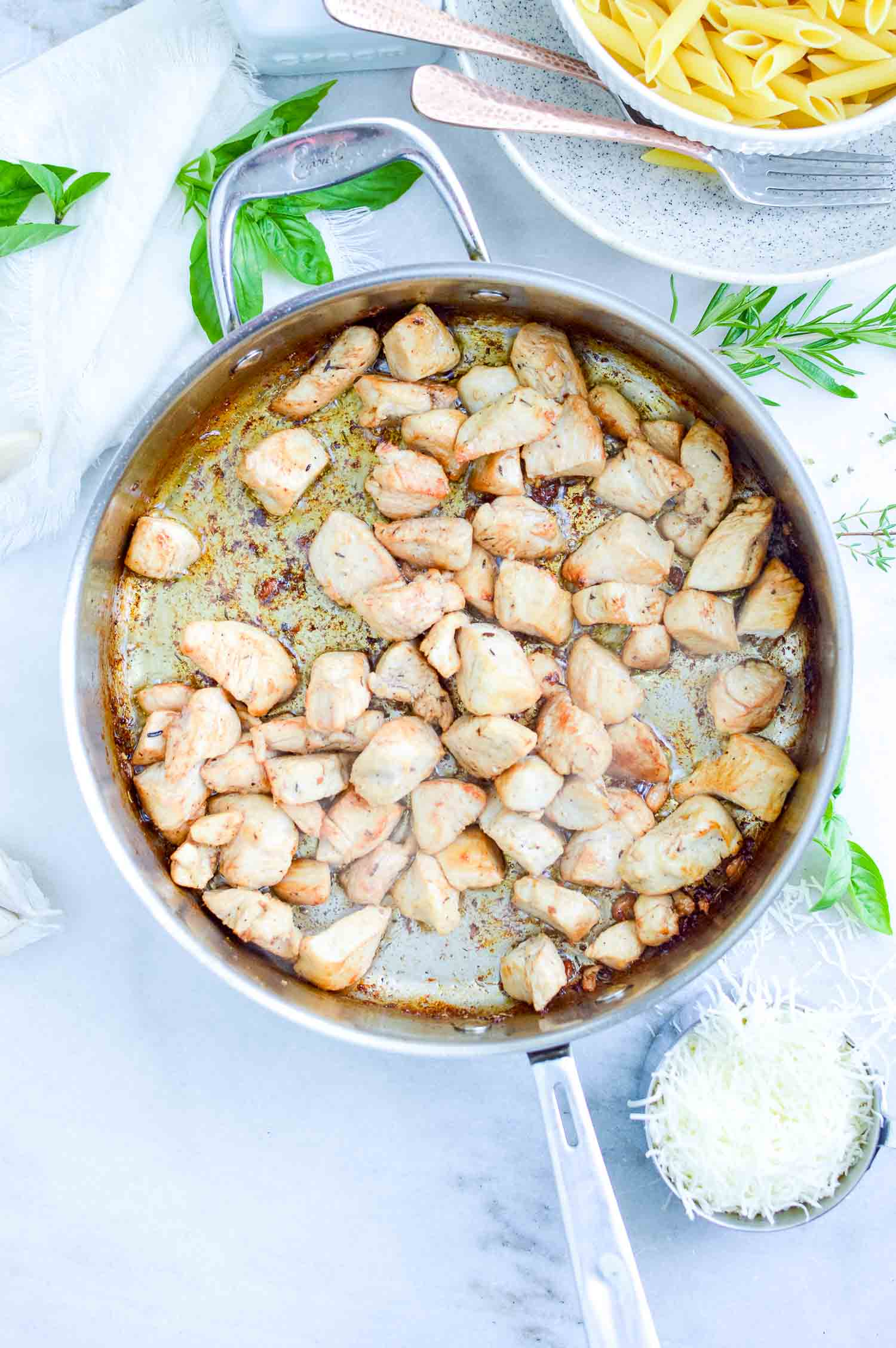 A silver pan with cooked cut chicken in it with fresh herbs around it and also a silver cup of shredded cheese.