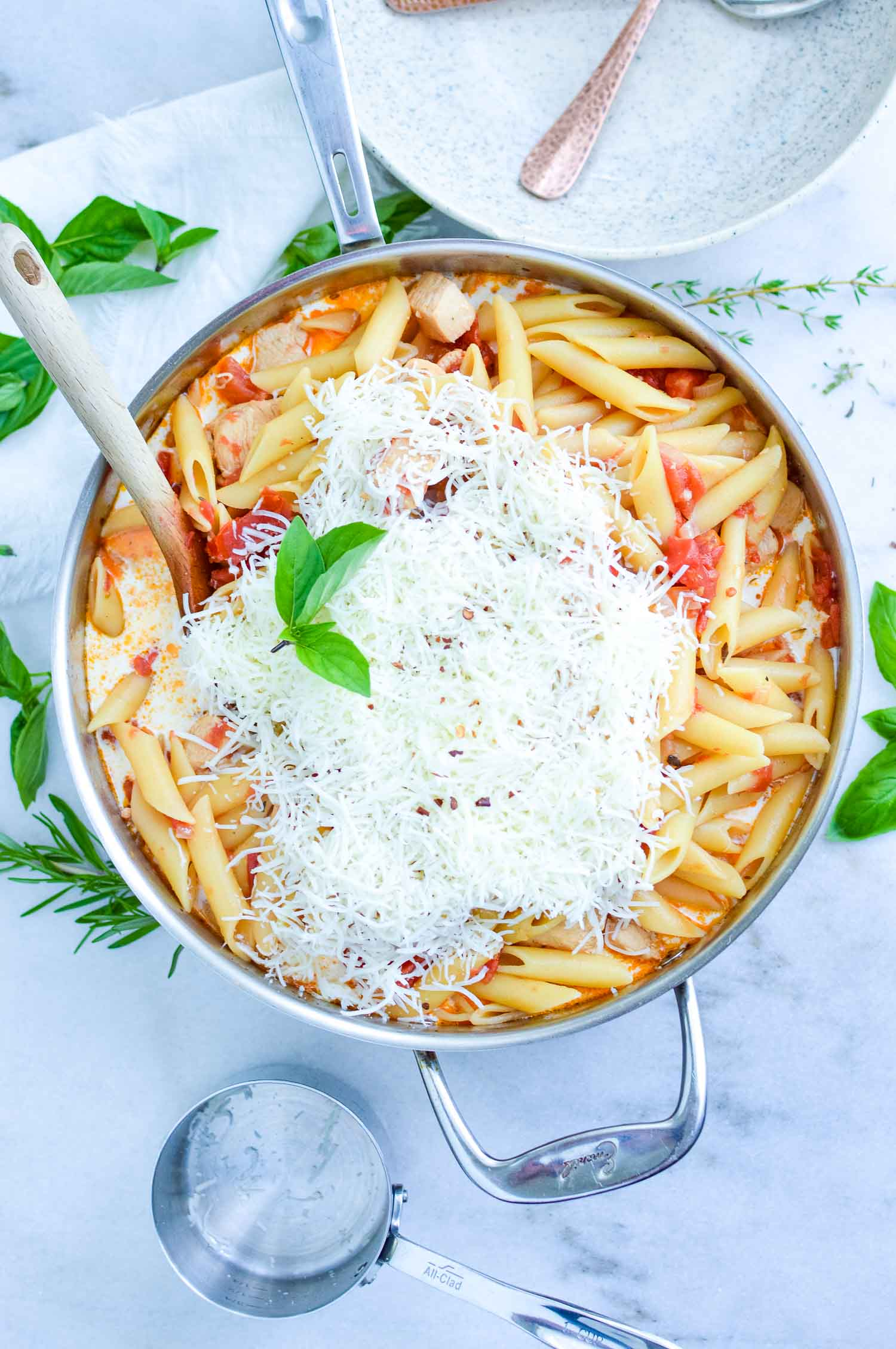 A silver pan of cooked penne pasta with cut tomatoes and half and half with shredded cheese on top of it along with a wooden spoon inside of it and fresh herbs around it and an empty measuring cup on the side.