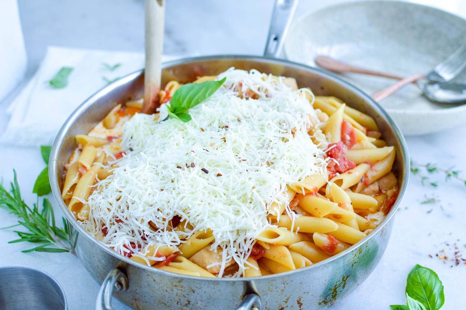 A silver pan full of pasta, shredded cheese, tomatoes and spices with a wooden spoon in it with fresh basil around the bowls.