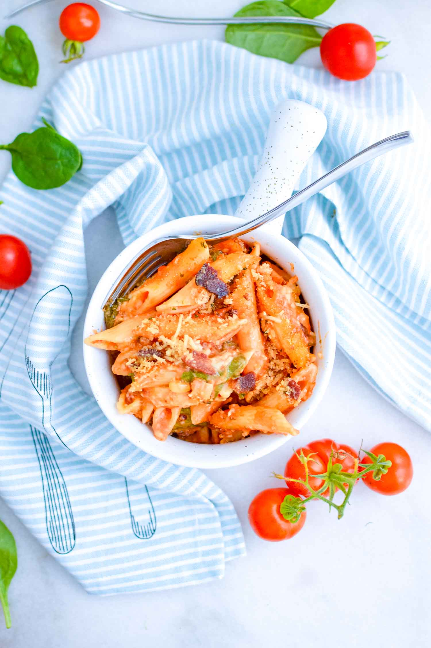 A white bowl full of pasta with a silver fork in it with a blue and white striped towel and basil and tomatoes around it.