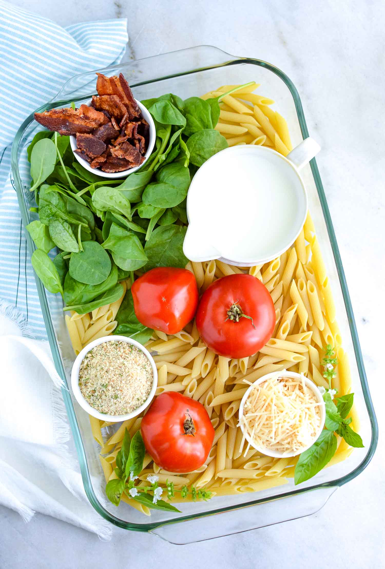 A glass pan with ingredients like pasta, bacon, tomatoes, bread crumbs, milk, cheese and spinach in it.