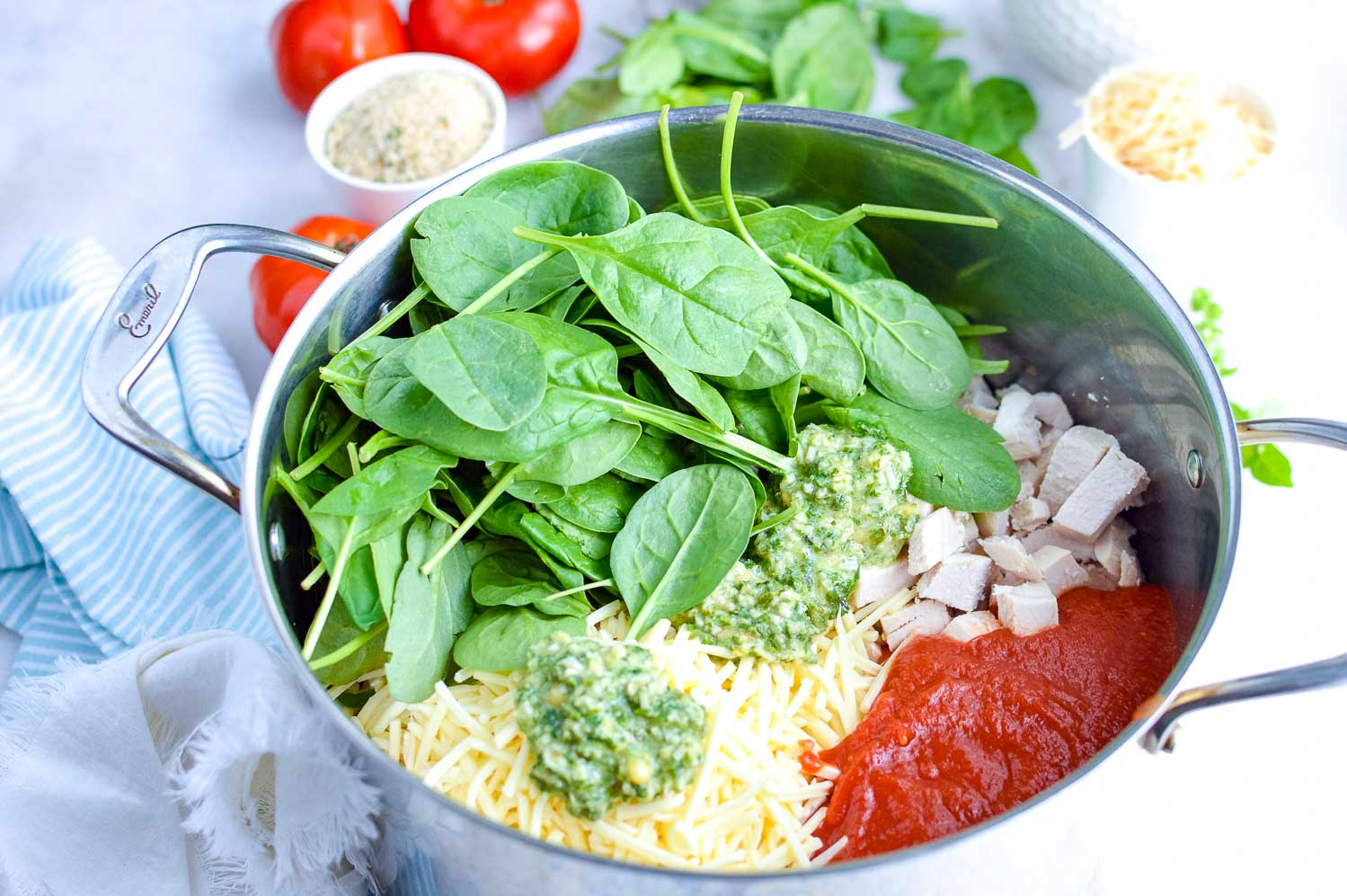 A stainless steel pot with ingredients in it like spinach, tomatoes, cheese, pesto and chicken with extra ingredients around it.