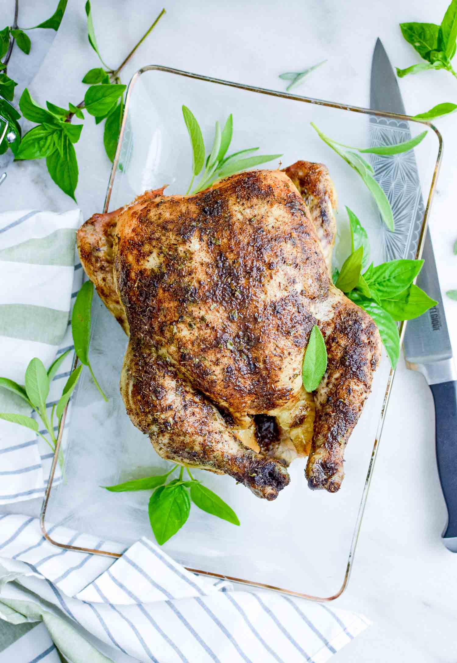 A whole roasted chicken on a clear tray with a metal knife and green herbs around it.