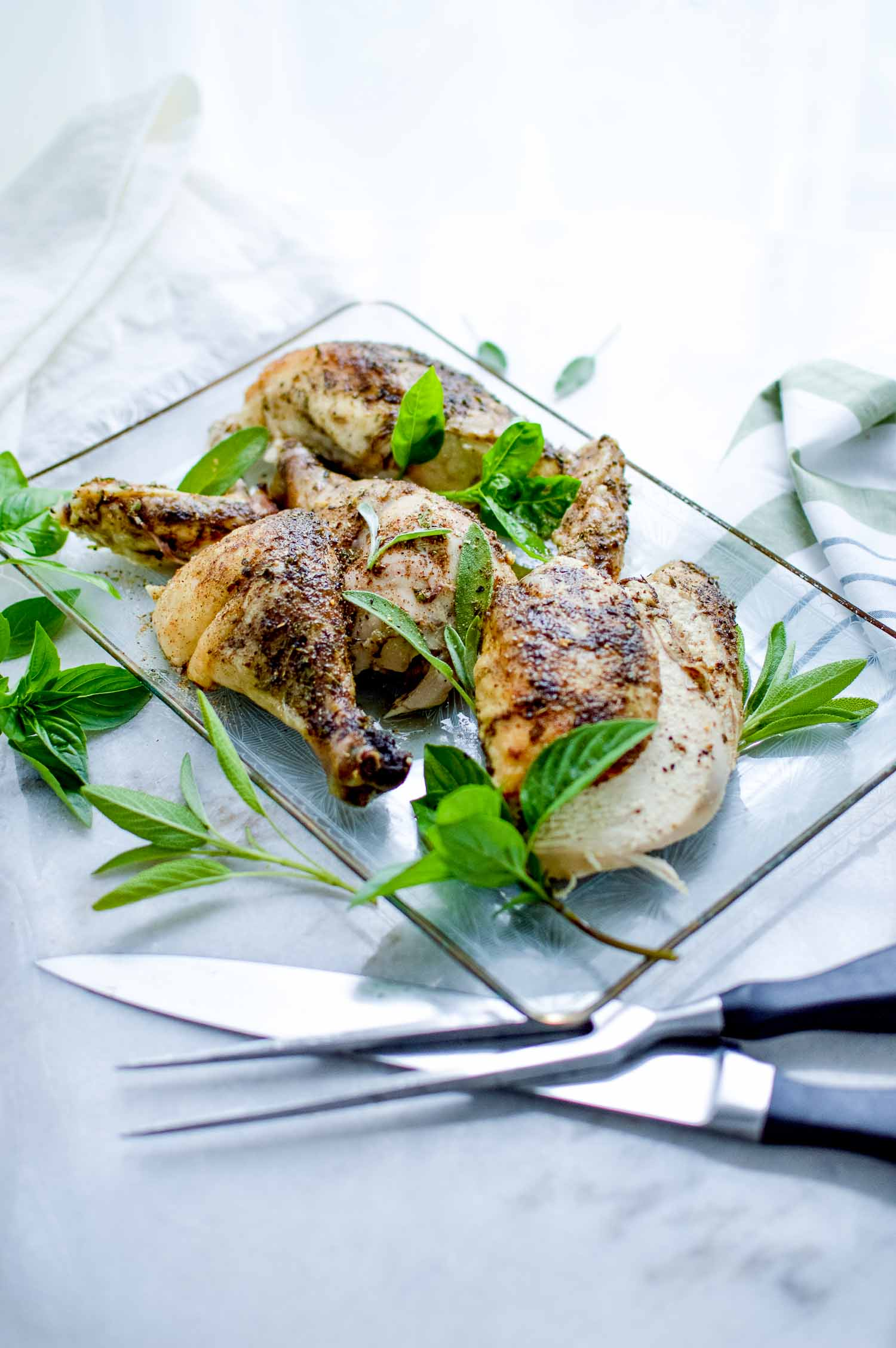 A clear tray with a cut seasoned chicken and green herbs all on and around it and a knife and prongs next to it.