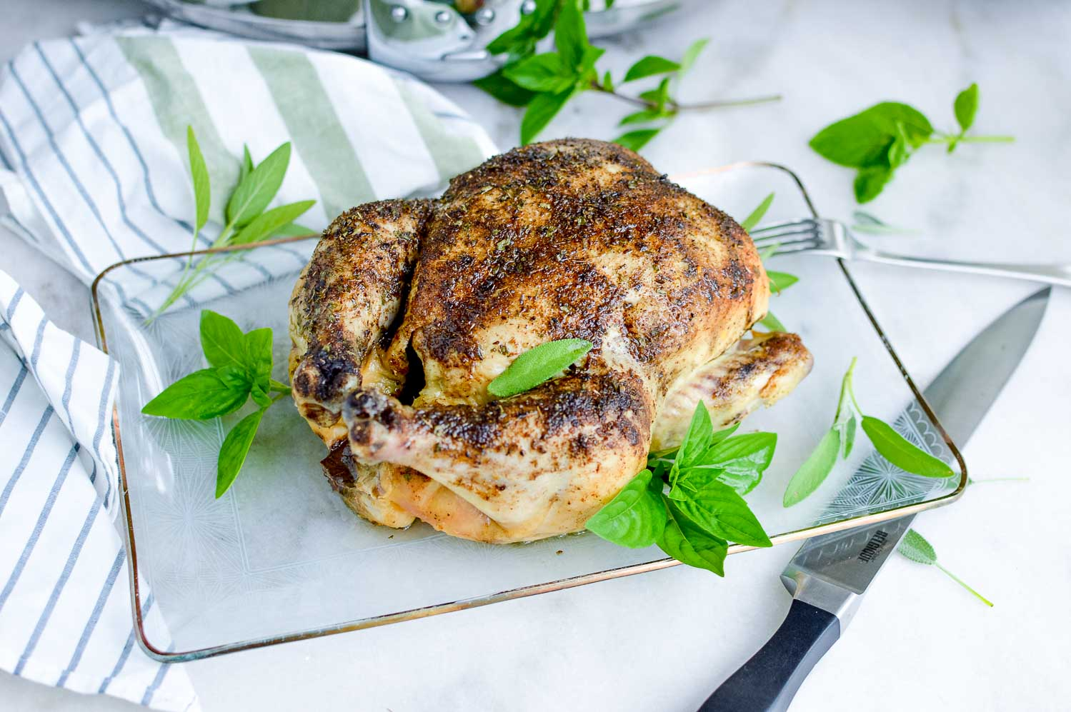 A whole roasted chicken on a clear tray with a metal knife and a fork and green herbs around it.