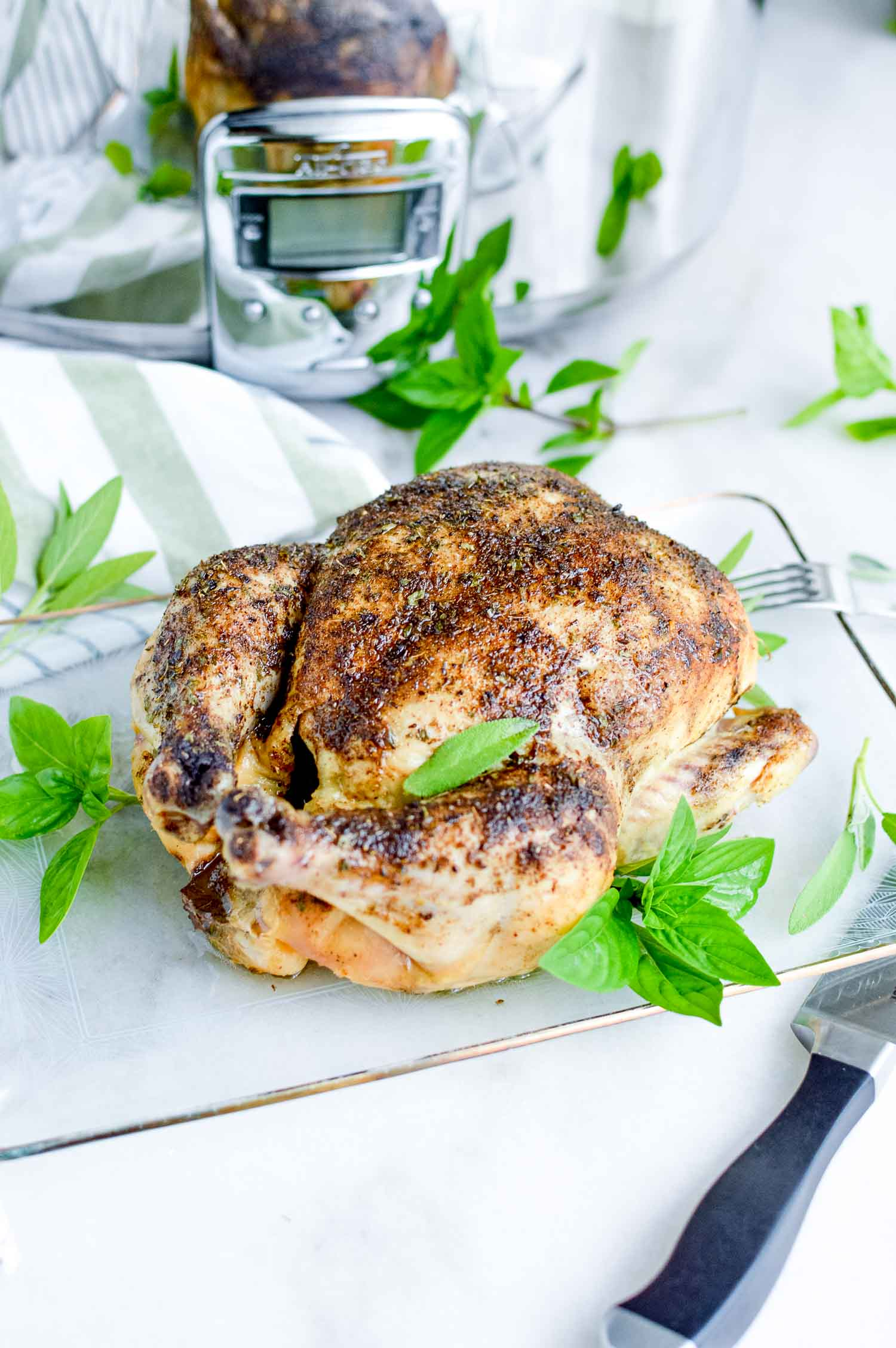 A slow cooker roast chicken on a clear tray with a metal knife and fork next to it and green herbs around and on top of it.
