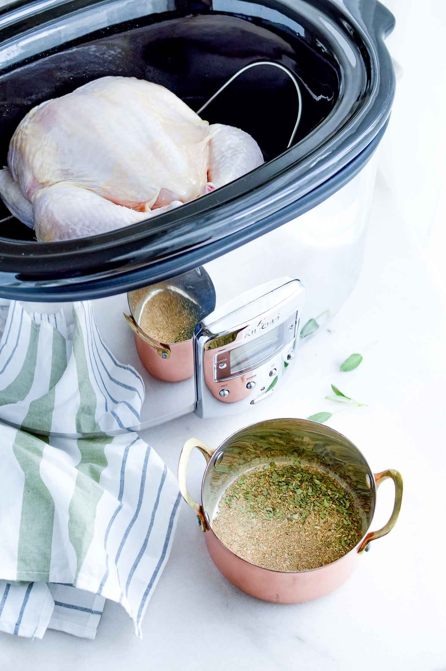 A slow cooker with a raw chicken in it and next to it a small metal bowl with seasonings in it.